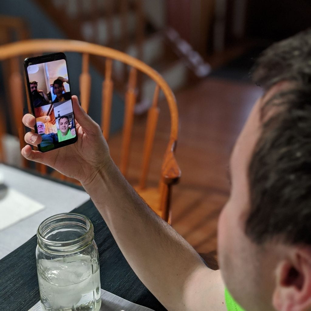 person video chatting with family at dinner table